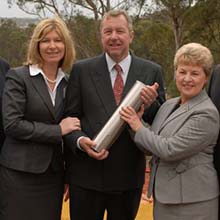 """HMRI Chair Bob Kennedy (centre) with representatives from HMRI, the University of Newcastle and Hunter New England Health, holding the """"Knowing"""" Time Capsule on the HMRI Building construction site."""