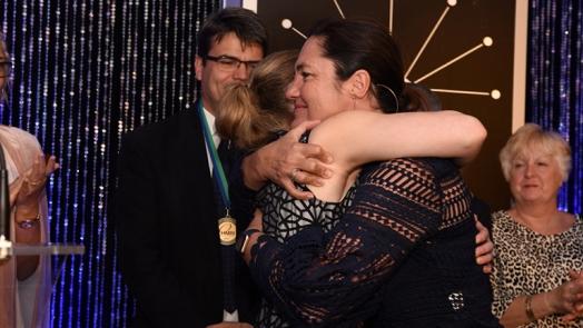 Anne Callander hugs Dr Kelly McKelvey during her Fellowship presentation